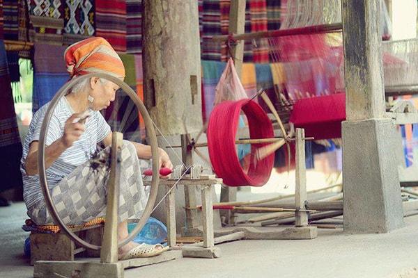 Hình ảnh người phụ nữ Thái ngồi trên hiên nhà sàn quay sợi để dệt vải thổ cẩm