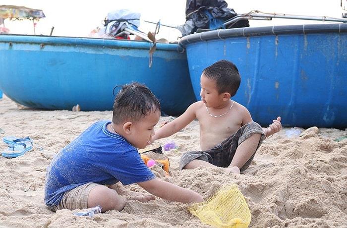 Những đứa trẻ nghịch cát trên bờ biển